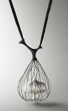 Ugliest necklace ever. Why do you want a caged mushroom around your neck?