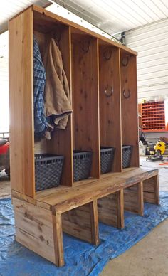 Western rustic front entryway / mudroom closet, boot storage, mitt, glove, toque storage and bench with horseshoe hangers.