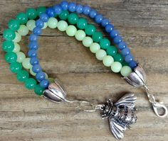 Bring a little brightness and cheer with you wherever you go! This adorable handmade beaded bracelet is made up of three strands of blue and green beads and finished with silver flower shaped bead cones and 1 1/2 inch bee charm. Bracelet measures 8 1/2 inches long.