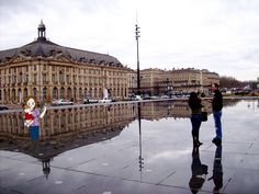 Bordeaux, France standing in the water mirror at Place de la Bourse in Port of the Moon. The water mirror is a giant rectangle of ½ thick water, enough water over a black granite  plaza to create a surface large enough to reflect the entire 18th century Stock Exchange building.