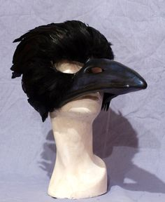 This mask was hand sculpted and cast in neoprene. Every feather is individually glued in place and they wrap around the back to enclose most of the
