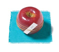 Thanksgiving Place Card: Wrap a thing gold cord around an apple several times.  Tie a knot in the back of the apple.  Slip a piece of paper with guest's name under the cord in front.