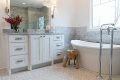Elegant white and gray bathroom is clad in gray quartrefoil cement floor tiles and features a rustic wood stool placed in front of a freestanding bathtub paired with a polished nickel floor mount tub filler.