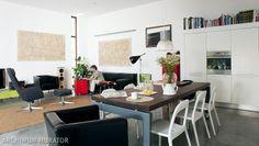Nowoczesny salon z kuchnią i jadalnią tworzą otwartą i wygodną przestrzeń dzienną. Nie ma tu wielu dekoracji. Wystrój salonu nawiązuje do stylu industrialnego przez podłogę, która została wykonana z betonu polerowanego. Oszczędne barwy w nowoczesnym salonie ożywiają dodatki w czerwieni.
