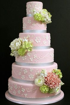Flowery piping, silver ribbon and a mix of white, pink and light green flowers give this soft pink cake an extra feminine touch.