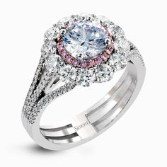 This lovely white gold contemporary ring features a dazzling halo of .10 ctw pink diamonds accented by 1.13 ctw round cut white diamonds.