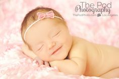 Newborn baby girl smiling with pink bow headband on pink floral fabric to infinity www.ThePodPhoto.com