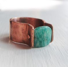 Like the color of a foamy sea, blue-green Russian Amazonite is flecked with black specks and white bands. This cushion cut 3/8 square stone is suspended with handmade rivets in a 3/8 wide copper band. Band is hand forged, hammered & sanded to a brushed finish, waxed inside an out to reduce oxidation. *Note: Currently custom made to your size: Specify size at time of purchase an allow an additional 10 business days to create. Note that each stone differs in color slightly.    Not...