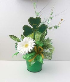 St Patricks Day arrangement comes in a bright green metal container. Filled with white, yellow and green gerbera daisies, deco mesh, shamrock ribbons and patricks day party gifts Your place to buy and sell all things handmade St Patrick's Day Crafts, Holiday Crafts, St Pattys, St Patricks Day, Saint Patricks, Green Centerpieces, Centrepieces, St Patrick's Day Decorations, St Paddys Day
