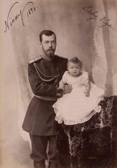 Nicolau II, Imperador da Rússia e Grã-duquesa Olga Nikolaevna. Nicholas II está em pé à esquerda apoiando a bebê Grã-duquesa Olga que está sentada em uma mesa alta coberta com um pano de veludo. Ele está vestindo uniforme militar e a bebê está vestindo um vestido com um babado de renda. Há uma cortina atrás. A fotografia é anotado 'Nicky 1896' e 'Baby Olga'.