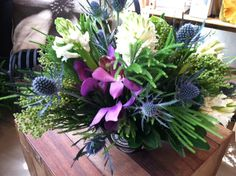 Orchids, thistle and greens--a unique arrangement of flowers for your home.