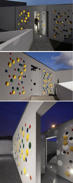 This home in Portugal, designed by Architect Nelson Resende, has a wall of holes that perforate the exterior entrance wall, and are filled with pops of color.