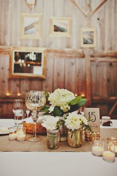 So beautiful! White flowers in individual mason jars as centerpiece