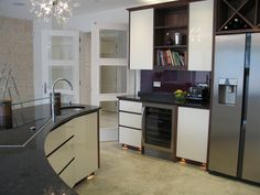 Showing the curve of the island unit and the bespoke toughened glass breakfast bar. Take a look at our website for more inspirational kitchens.