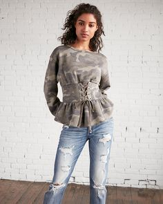 Take on the trends with this sweatshirt that combines a cool camo print with an adjustable lace-up front and peplum hem. It takes laid-back street style to a whole new level of comfort and style.