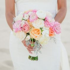The bride carried a bouquet of pink, orange and ivory roses down the beachfront aisle.