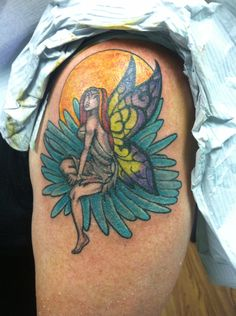 My fairy sitting on aster flower with a yellow orange sun my 11th tattoo on my left upper arm for my 50 th bday
