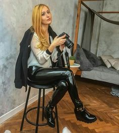 Photographer in casual black latex pants and ankle boots