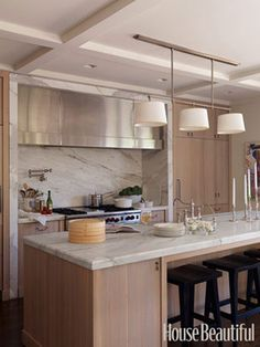 To balance the oak cabinets in his Los Angeles kitchen, designer William Hefner topped the counters and framed the range area with a warm Calacatta gold marble, for a style that's still soft.