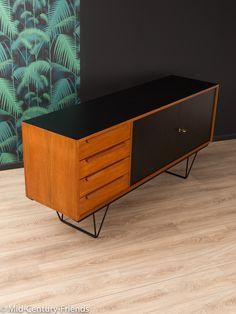 Klassisches Sideboard aus den 1960er Jahren. Hochwertiger Korpus in Teak Furnier mit vier Schubladen, zwei resopalbeschichteten Schranktüren in schwarz, einem Boden und neuen, filigranen...