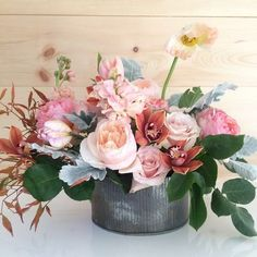 Medium-larger arrangement. vessel designer's choice Flowers could include: garden roses, ranunculus, stock, tulips, hellebores, sweet peas, poppies and/or other lovely accents with dusty miller and co