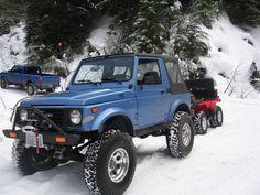 Blue soft top suzuki samurai on snow