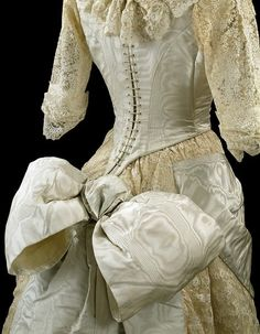 Ball gown, British, ca. 1885. Bodice & skirt are moir� silk overlaid & trimmed w/machine-made lace. Bodice is heavily boned & very close-fitting; has narrow waist and is laced at back to resemble a corset. The deep point of the bodice gracefully curves over the back of the skirt. Neckline is low and square at the front and rounded at the back and trimmed with a fall of lace. Lined w/silk, cotton, & whalebone strips. Made for May Primrose by oldrose