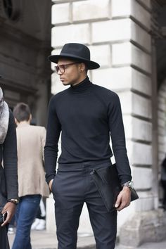 Charcoal trousers, black polo neck, black hat, black leather document walet