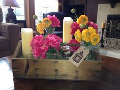 an antique tool caddy filled with seasonal flowers, candles and birds' nest with embossed tag.  makes a great coffee table centerpiece for spring and summer