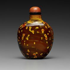 A 'REALGAR' GLASS BOTTLE 18TH/19TH CENTURY  ~  The bottle is of flattened, ovoid form and of a reddish-brown tone accented with brilliant splashes of ochre and orange.