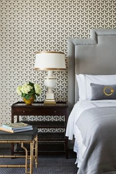 chic modern hollywood regency bedroom with brass bamboo upholstered stool, upholstered bedhead, geometric wallpaper, and white table lamp