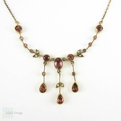 (http://www.addysvintage.co.uk/antique-tourmaline-split-pearl-floral-design-necklace-9-carat-gold-with-beaded-detailing-edwardian-circa-1900s/)