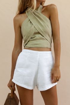 Sophistication is key. This is a cropped top that ties at the neck. Halter neck top Straight across bandeau with front waist darts and back elastic Attached fabric on both sides, ties at neck Cropped Open back Material: 100% linen Model wears size XS