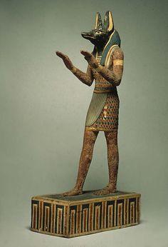Cette statuette représente Anubis, le dieu égyptien des morts et du rituel de la momification, maître des nécropoles et protecteur des embaumeurs, avec un corps humain & une tête de canidé, chien ou chacal. Il porte le costume de plumes traditionnel des divinités égyptiennes. Il se tient avec les mains en avant, les paumes vers le bas; une position fréquente lorsqu'il exécute les rituels de purification & de transfiguration sur une momie.
