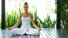 stock-footage-stylish-beautiful-woman-in-lotus-position-sitting-meditating-on-a-wooden-deck-with-a-backdrop-of