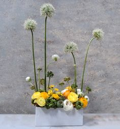 """High & Low  Arrangements are no longer just one note: tall or short. Set out a conversation piece like this mod mix that stands tall and short, with yellow ranunculus hunkering in the box seats. It's style that doesn't take itself too seriously. """"Start with a carpet flower for support,"""" advises Clover. """"Then add big, tall blooms."""""""