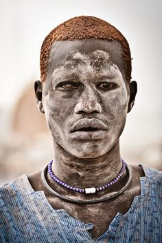 A Mundari male covered in ash and orange hair bleached in the sun from washing it in cow urine.