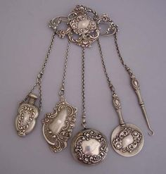 """Sterling chatelaine with pin back, 3-1/2"""" wide with five 3-4"""" chains; 3"""" glove hook, 3"""" mirror, 2"""" perfume, 2-3/4"""" aide memoire or notepad; 1-5/8"""" wide and 3/4"""" deep silver flowers and scrolls repousse pill box engraved """"Myra March '98"""" with hallmark for Gorham 1897, one dimple on back. Each piece has an embossed flowers and scrolls motif."""