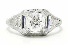 The Gilbert Antique Edwardian Diamond Engagement Ring is mounted with a fiery, sparkling, over 1 carat Old European cut brilliant in a classic solitaire accented with calibre' blue sapphires. The charm of these hand cut antique gems is unmistakeable and the attention to detail with the filigree, pierced setting makes for a true heirloom experience for a unique bridal ring. #edwardian #diamond #engagementring #platinum #edwardianring #edwardianrings #estatejewelry #estatejewelery #antiquering Estate Engagement Ring, Antique Engagement Rings, Antique Rings, Diamond Engagement Rings, 1 Carat, Round Diamond Ring, Round Diamonds, Estate Jewelery, Edwardian Ring
