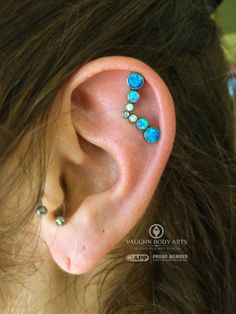 Elizabeth stopped in wanting a piercing, but she wasn't quite sure what she wanted. Few things are as awesome as a client asking what we think would look best.Elizabeth had the perfect ear for this lovely two-point 14g cluster from anatometal. Dark blue opals, light blue opals, white opals, and a tiny little CZ. Seven gorgeous gems, but only two piercings required!