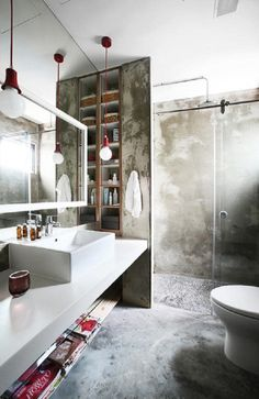 like the cement screed wall and shelving, would prefer concrete counter top, like full mirror with white frame focus in front of sink, like sliding door shower screen - Interior Designer: 19sixtyseven  The raw concrete walls and floor, coupled with the hanging lights give the toilet an industrial, unfinished look. The in-wall compartments and shelving under the sink also means less clutter on the counter.  - Interior Designer: 19sixtyseven