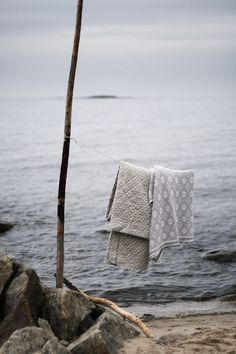 Rustic summer on the beach. Natural color cotton blankets dry by the water. So serene!