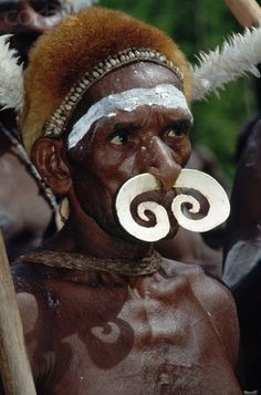 A man from the Asmat tribe from the south coast of Irian Jaya, Indonesia, wears a nasal ornament made of sharpened nacre. | Image and caption © Charles & Josette Lenars