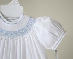 Adorable dress from Feltman Brothers' line Freidknit Creations. White batiste smocked bishop dress with lovely detailing. Finely detailed zig zag blue smocking