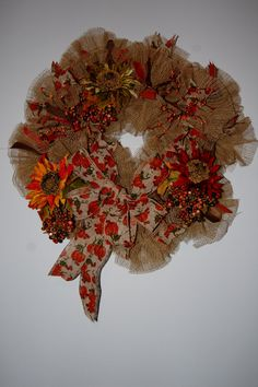This wreath measures approximately 30 inches and is made of Deco Mesh burlap, wired ribbons in orange, green and brown, a large burlap bow