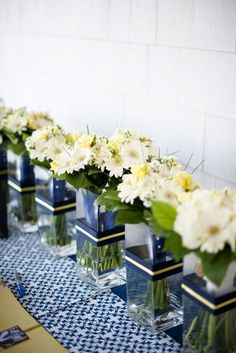 Simple, square vases wrapped in wedding color ribbon.