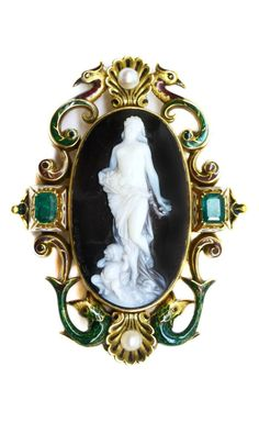 19th century gold, enamel and gem set cameo brooch by Ernesto Pierret, Italian c.1860, the oval white on brown agate featuring a semi-clad lady bearing flower basket with a cherub at her feet, signed 'G.A. Girardet F' and 'G. Ciniselli Inv.', within a peacock and fish scroll frame with pearl set scallop shells, emeralds to either side, green, red and white enamel decoration.  At SJ Phillips.