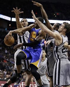 Golden State Warriors' Andre Iguodala (9) passes as San Antonio Spurs' Tim Duncan (21), Tiago Splitter (22) and Kawhi Leonard, second from right, defend during the second half of an NBA basketball game, Friday, Nov. 8, 2013, in San Antonio. San Antonio won 76-74. (AP Photo/Eric Gay)