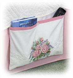 A cross-stitch rose pillowcase becomes a pretty and handy bed caddy in this fun project. Use this caddy to stash books, reading glasses or the remote. You can also use this same concept to create a Rose Chair Caddy.