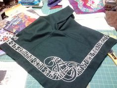 Norse hood (Skjold) in green wool with embroidery design based off of several different rune stones.